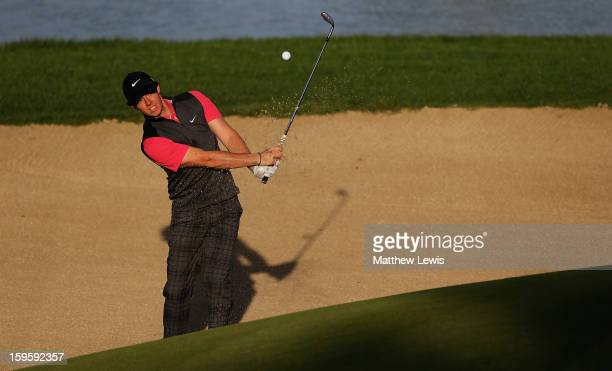 Rory McIlroy of Northern Ireland plays out of a bunker on the 12th hole during day one of the Abu Dhabi HSBC Golf Championship at Abu Dhabi Golf Club...
