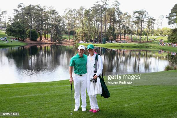 Rory McIlroy of Northern Ireland poses alongside his caddie/girlfriend Caroline Wozniacki during the 2014 Par 3 Contest prior to the start of the...