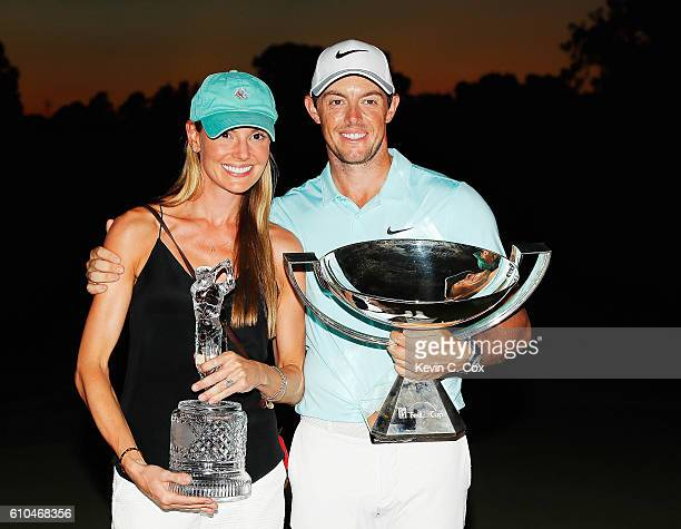Rory McIlroy of Northern Ireland poses alongside his girlfriend Erica Stoll and the FedExCup and TOUR Championship trophies after his victory over...