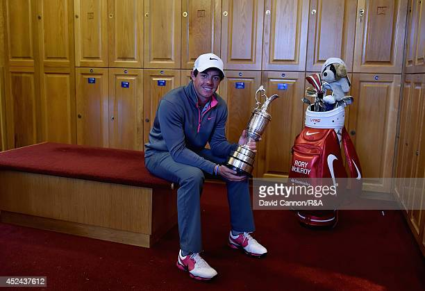 Rory McIlroy of Northern Ireland poses with the Claret Jug in the locker room after his two-stroke victory in The 143rd Open Championship at Royal...