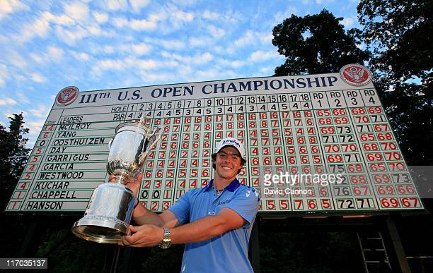 Rory McIlroy of Northern Ireland poses with the trophy after his eight-stroke victory on the 18th green during the 111th U.S. Open at Congressional...