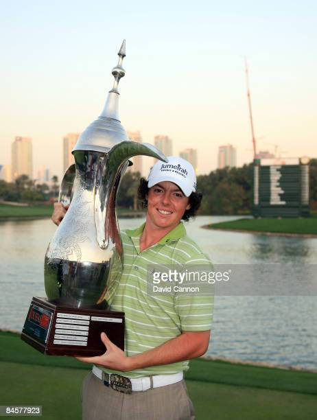 Rory McIlroy of Northern Ireland poses with the trophy after winning the 2009 Dubai Desert Classic on the Majilis Course at the Emirates Golf Club on...