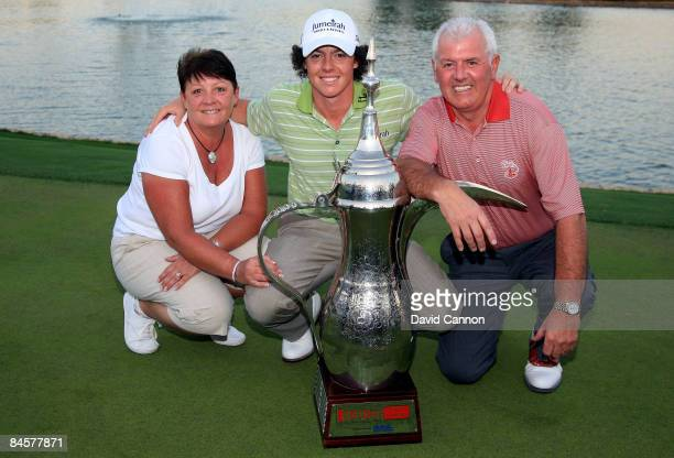 Rory McIlroy of Northern Ireland poses with the trophy alongside his parents Rosie and Gerry after winning the 2009 Dubai Desert Classic on the...