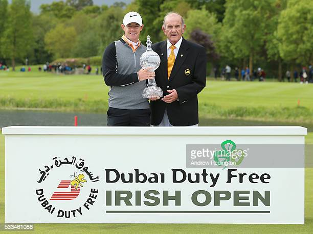 Rory McIlroy of Northern Ireland poses with the trophy with Colm McLoughlin the Executive Vice Chairman of Dubai Duty Free after winning the Dubai...