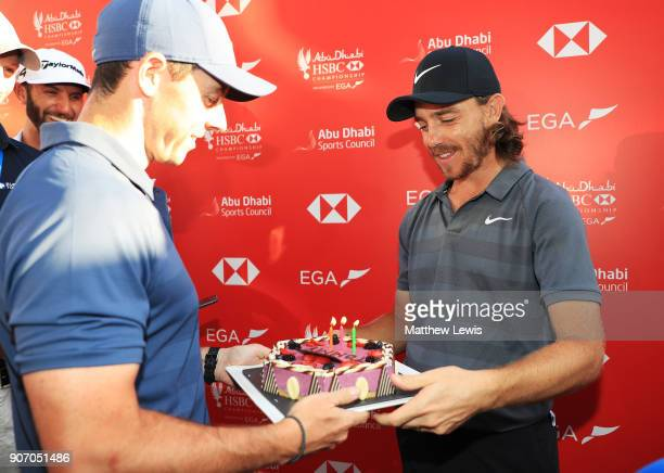 Rory McIlroy of Northern Ireland presents Tommy Fleetwood of England with a cake for his birthday after round two of the Abu Dhabi HSBC Golf...