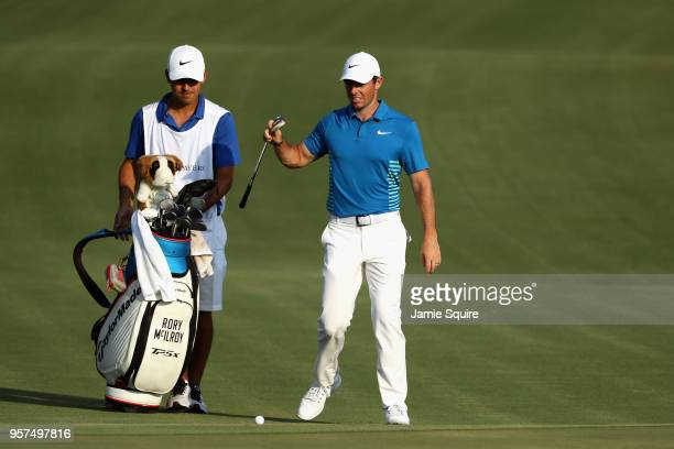 Rory McIlroy of Northern Ireland pulls a club from his bag as he prepares to play a shot as caddie Harry Diamond looks on on the 18th hole during the...