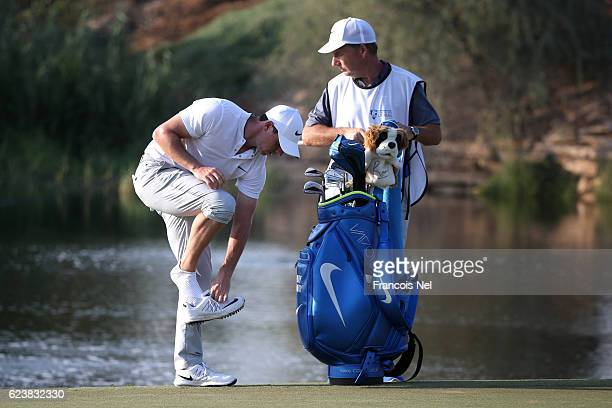 Rory McIlroy of Northern Ireland puts his shoes back on after playing his 4th shot on the 16th hole during day one of the DP World Tour Championship...