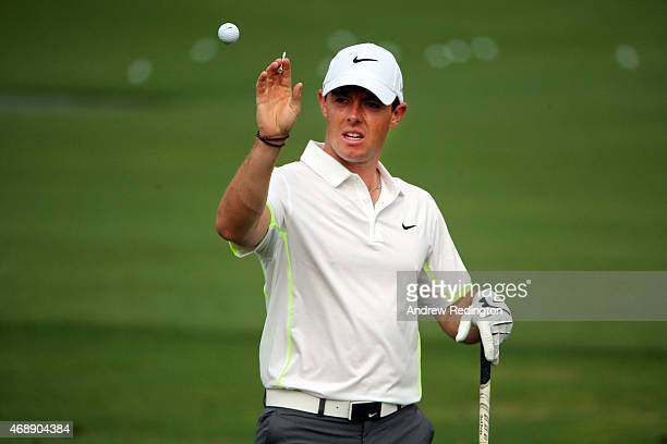 Rory McIlroy of Northern Ireland reaches for a golf ball on the practice ground during a practice round prior to the start of the 2015 Masters...