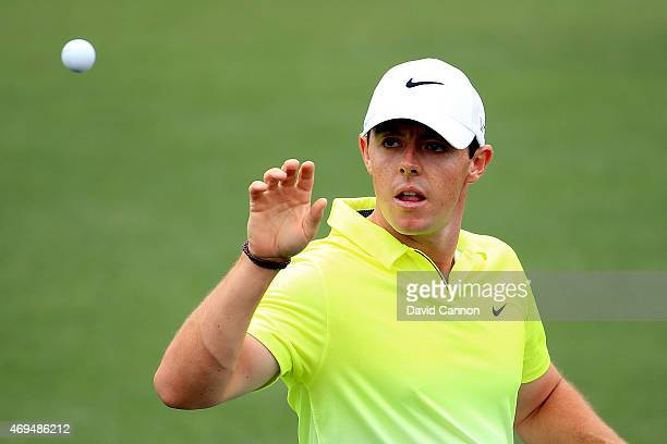 Rory McIlroy of Northern Ireland reaches for a golf ball on the practice ground during the final round of the 2015 Masters Tournament at Augusta...