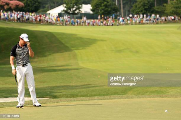 Rory McIlroy of Northern Ireland reacts after putting on the first green during the third round of the 93rd PGA Championship at the Atlanta Athletic...