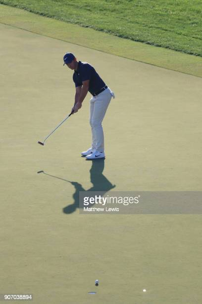 Rory McIlroy of Northern Ireland reacts as he watches his eagle putt on the 18th green during round two of the Abu Dhabi HSBC Golf Championship at...