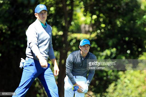 Rory McIlroy of Northern Ireland reacts to his shot from the second tee as Jordan Spieth of the United States walks from the tee during the third...