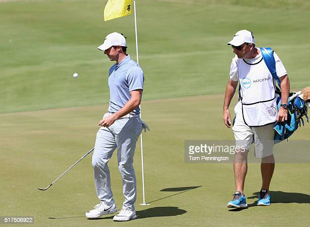Rory McIlroy of Northern Ireland reacts to losing the 16th hole as his caddie JP Fitzgerald looks on during the third round of the World Golf...