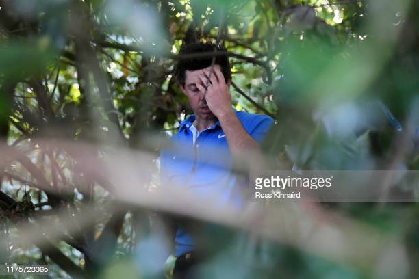 Rory McIlroy of Northern Ireland reacts within some trees on the 18th hole during Day One of the BMW PGA Championship at Wentworth Golf Club on...