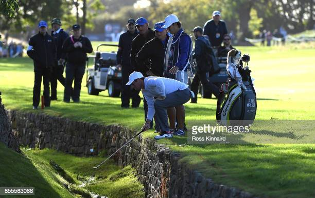 Rory McIlroy of Northern Ireland retrieves his ball from a hazard on the 14th hole during day two of the British Masters at Close House Golf Club on...