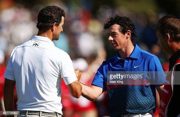 Rory McIlroy of Northern Ireland shakes hands with Adam Scott of Australia after sinking his birdie putt on the 18th hole to claim victory during day...