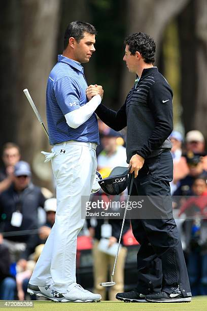 Rory McIlroy of Northern Ireland shakes hands with Gary Woodland on the 16th hole green after winning their championship match 42 in the World Golf...