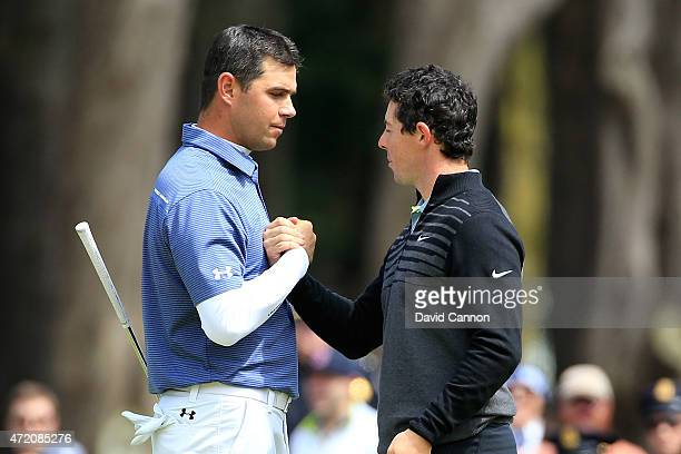 Rory McIlroy of Northern Ireland shakes hands with Gary Woodland on the 16th hole green after winning their championship match 4&2 in the World Golf...