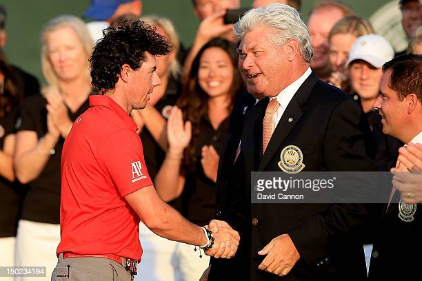 Rory McIlroy of Northern Ireland shakes hands with PGA of America Honorary President Jim REmy during the Final Round of the 94th PGA Championship at...