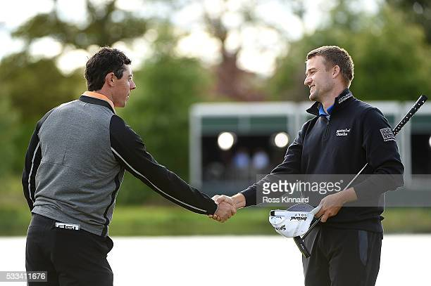 Rory McIlroy of Northern Ireland shakes hands with Russell Knox of Scotland on the 18th green following his victory during the final round of the...