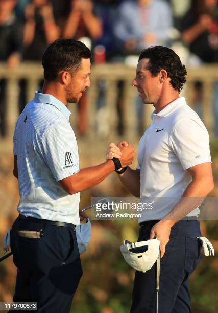 Rory McIlroy of Northern Ireland shakes hands with Xander Schauffele of the United States after his victory in a playoff on the 18th green during Day...