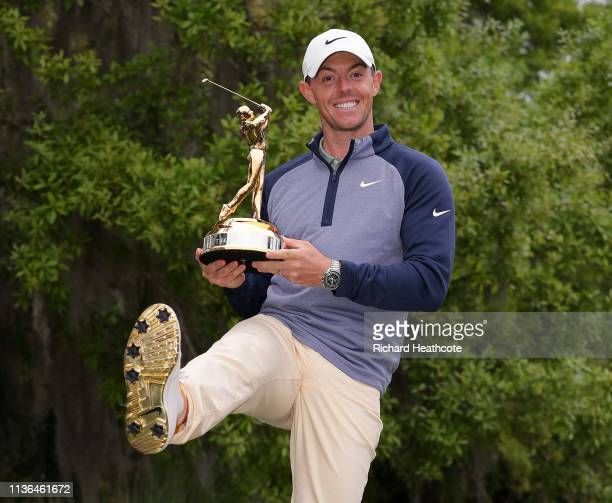 Rory McIlroy of Northern Ireland shows how the sole of his shoes matches the winner's trophy after winning The PLAYERS Championship on The Stadium...