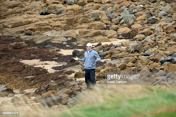 Rory McIlroy of Northern Ireland signals to his playing partner Ernie Els that he has found Els's ball on the rocks on the beach but it is unplayable...