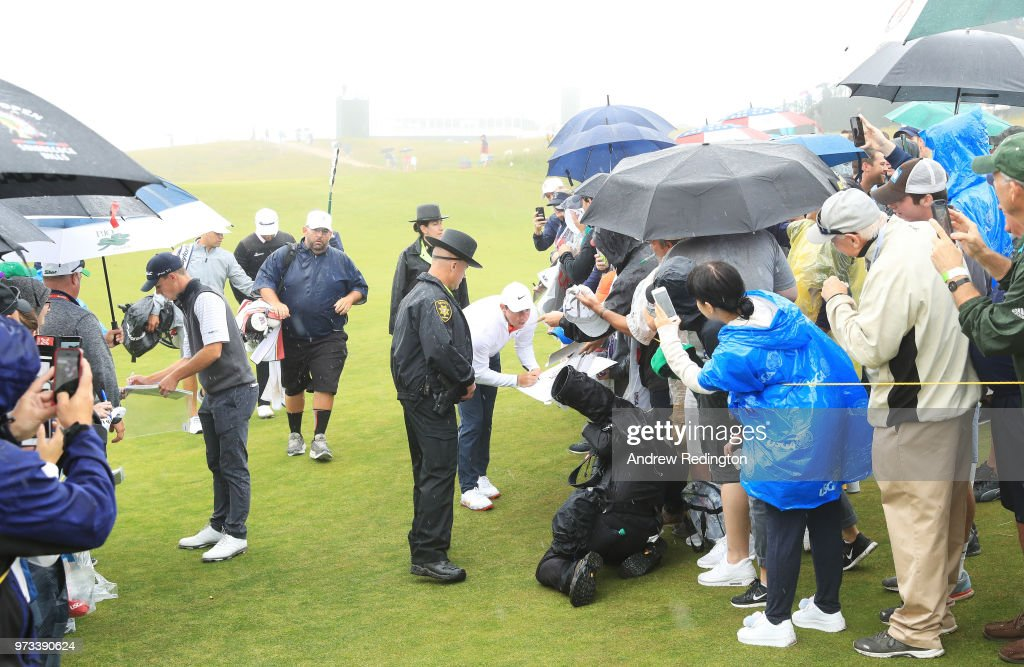 Rory McIlroy of Northern Ireland signs his autograph for a fan on the tenth hole during a practice round prior to the 2018 U.S. Open at Shinnecock Hills Golf Club on June 13, 2018 in Southampton, New York.