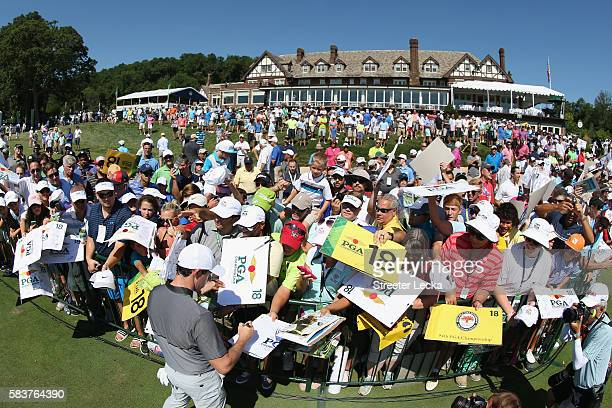 Rory McIlroy of Northern Ireland signs his autograph for fans during a practice round prior to the 2016 PGA Championship at Baltusrol Golf Club on...
