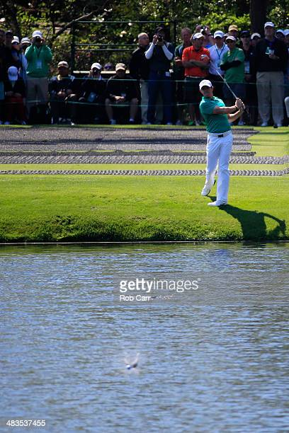 Rory McIlroy of Northern Ireland skips a ball across a pond on the 16th hole during a practice round prior to the start of the 2014 Masters...
