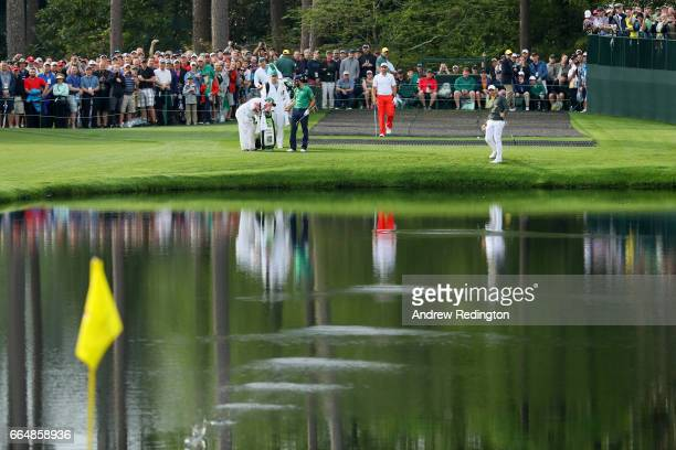 Rory McIlroy of Northern Ireland skips his ball across the pond on the 16th hole during a practice round prior to the start of the 2017 Masters...