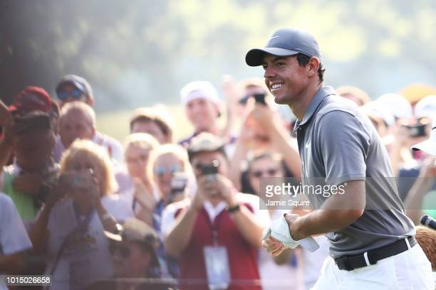 Rory McIlroy of Northern Ireland smiles after holing out on the 14th hole during the continuation of the weather delayed second round of the 2018 PGA...