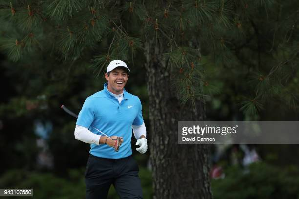 Rory McIlroy of Northern Ireland smiles after playing his second shot on the fifth hole during the third round of the 2018 Masters Tournament at...