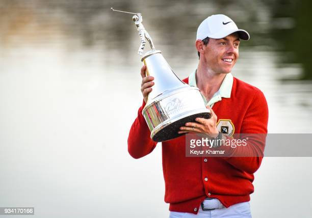 Rory McIlroy of Northern Ireland smiles and holds the tournament trophy while wearing a replica Arnold Palmer red cardigan following his three stroke...