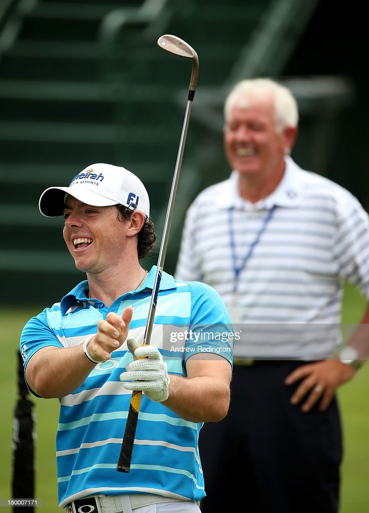 Rory McIlroy of Northern Ireland smiles as his dad Gerry McIlroy looks on during a practice round of the 94th PGA Championship at the Ocean Course on August 8, 2012 in Kiawah Island, South Carolina.