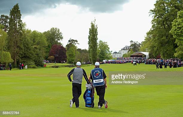 Rory McIlroy of Northern Ireland stands with his caddie JP Fitzgerald as he prepares to play his second shot on the 16th hole during the final round...