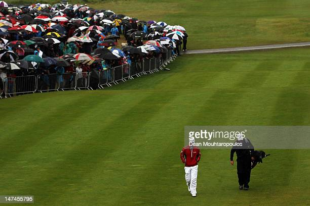 Rory McIlroy of Northern Ireland surrounded by fans holding their umbrellas walks towards the 1st tee during Day Three of the 2012 Irish Open held on...
