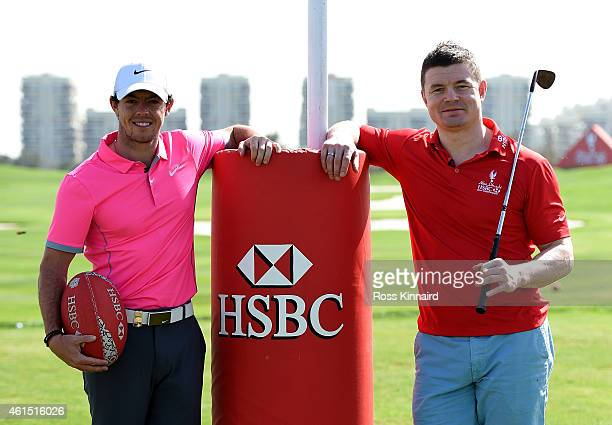 Rory McIlroy of Northern Ireland swaps sports with rugby legend and HSBC Sporting Ambassador Brian O'Driscoll during the proam event prior to the Abu...