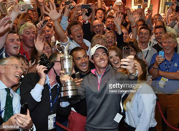 Rory McIlroy of Northern Ireland takes a selfie with the Claret Jug and members of Royal Liverpool in the clubhouse after his twostroke victory in...