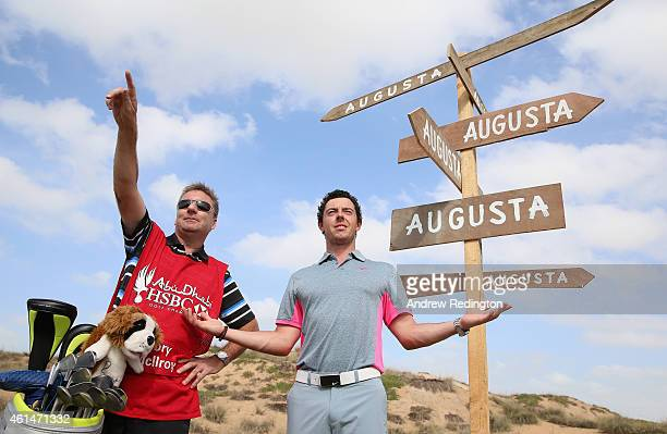 Rory McIlroy of Northern Ireland takes some advice from his caddie JP Fitzgerald during a photocall during practice prior to the start of the Abu...