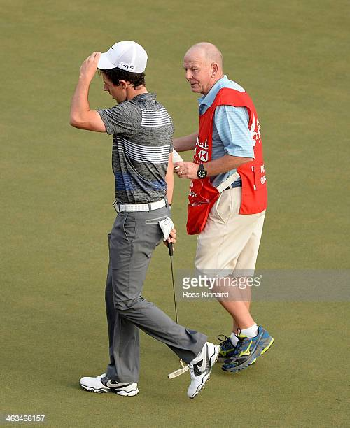 Rory McIlroy of Northern Ireland taliking to caddie Dave Renwick on the 18th green after he was informed of a possible rules issue during the third...