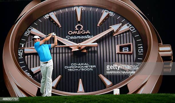 Rory McIlroy of Northern Ireland tees a shot in front of a giant advert depicting a watch during the third round of the 2014 Omega Dubai Desert...