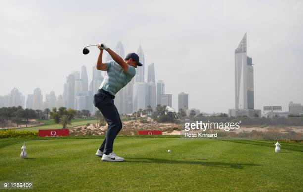 Rory McIlroy of Northern Ireland tees off on the 8th hole with the city as a backdrop during the final round on day four of the Omega Dubai Desert...