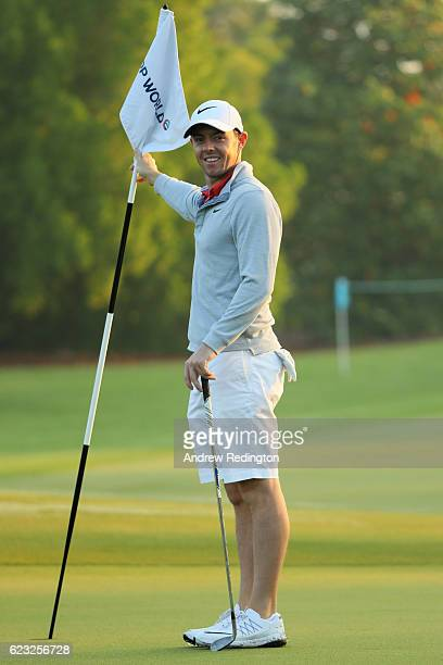 Rory McIlroy of Northern Ireland tends the flag on the 1st hole during a proam round ahead of the DP World Tour Championship at Jumeirah Golf Estates...