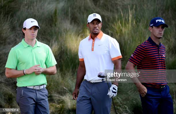 Rory McIlroy of Northern Ireland, Tiger Woods of the United States and Billy Horschel of the United States wait on a tee box during a practice round...