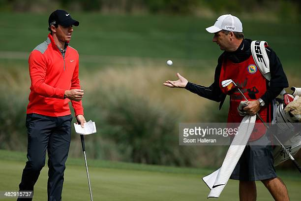 Rory McIlroy of Northern Ireland tosses the ball to his caddy JP Fitzgerald on the eleventh hole during round three of the Shell Houston Open at the...