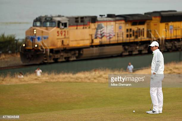 Rory McIlroy of Northern Ireland waits on the 16th green as a train passes behind during the first round of the 115th US Open Championship at...