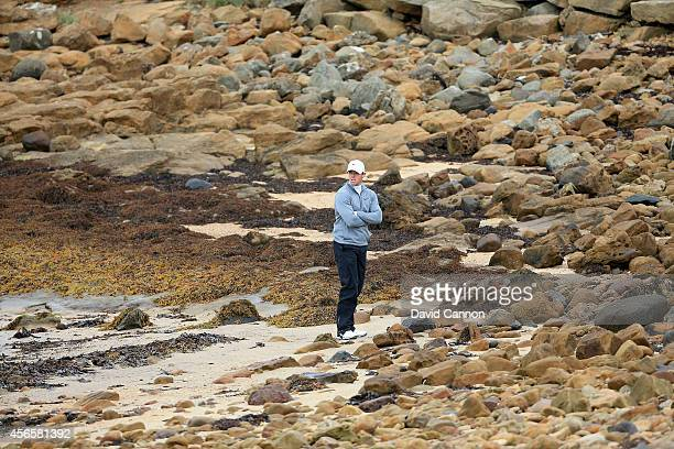 Rory McIlroy of Northern Ireland waits on the beach as his playing partner Ernie Els plays his fourth shot on the par 5 12th hole after McIroy had...