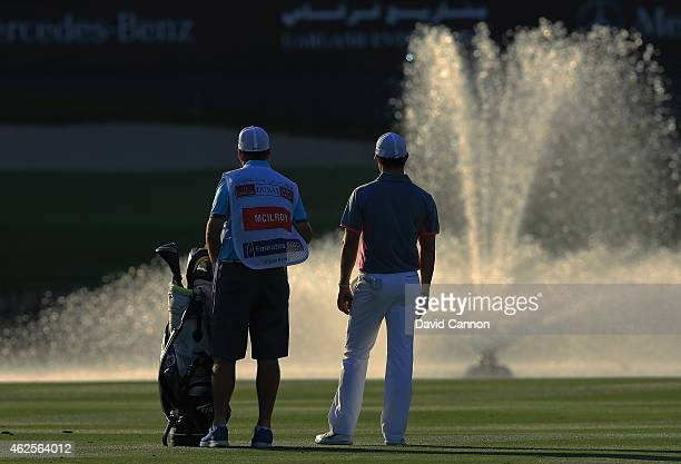 Rory McIlroy of Northern Ireland waits to play his fourth shot at the par 5 18th hole after his second shot had landed in the water guarding the...