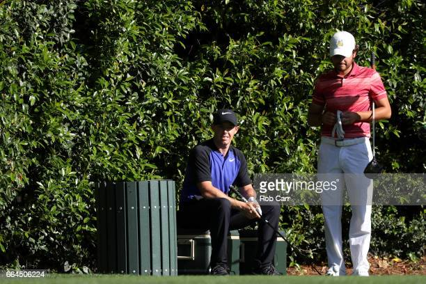 Rory McIlroy of Northern Ireland waits to tee off on the fifth hole as amatuer Toto Gana of Chile stands on the tee during a practice round prior to...